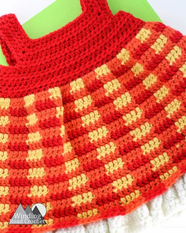 Crochet along with us with this free crochet pattern for a fall inspired crochet baby dress. This pattern has been designed for beginners with video tutorials for every part. Create this beautiful plaid baby dress with us. #crochetbabydress #crochetdress #freecrochetpattern