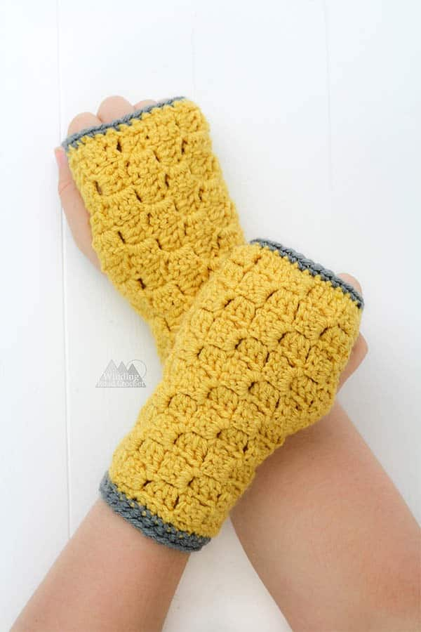Make these quick c2c fingerless gloves using the corner to corner crochet stitch for a beautiful texture. There are links to the photo and video tutorials for the corner to corner crochet stitch and a free pattern for the fingerless gloves. These are a wonderful fall crochet or winter crochet item. They would up fast and make great gifts. #crochetpattern #crochetgloves