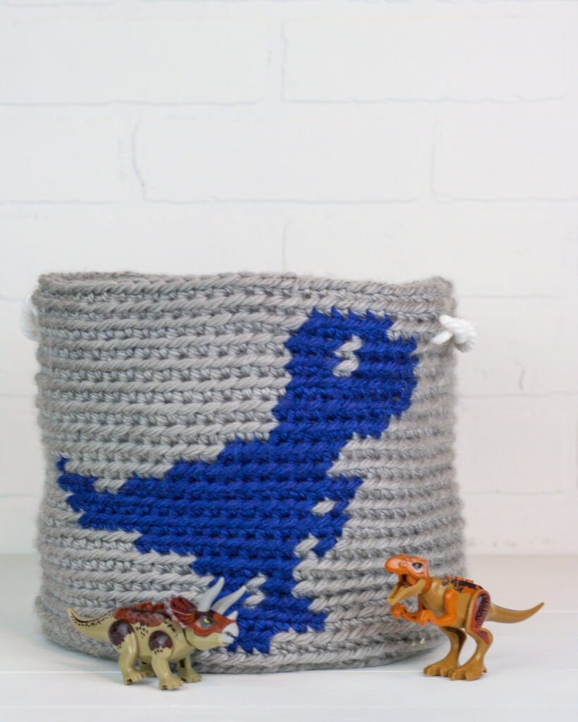 Quick and easy dinosaur basket crochet pattern by Winding Road Crochet with video guide.
