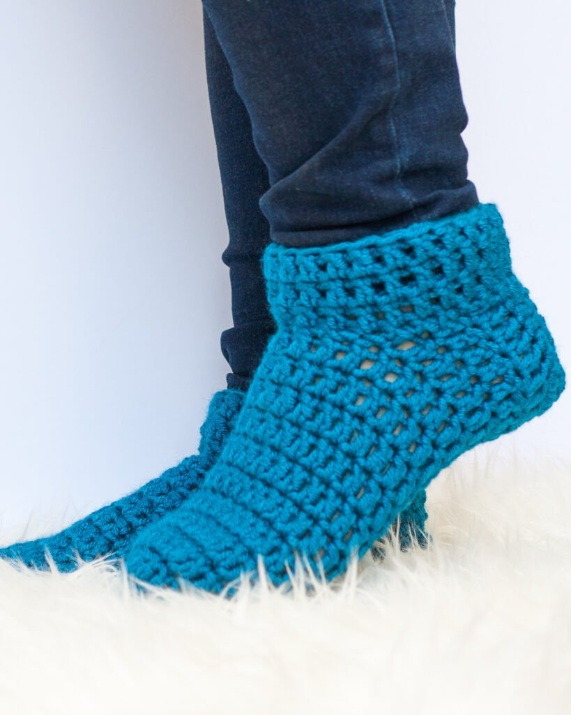 Want to make a pair of warm and cozy socks? This free pattern and video tutorial will teach you how to crochet slipper socks in under an hour.
