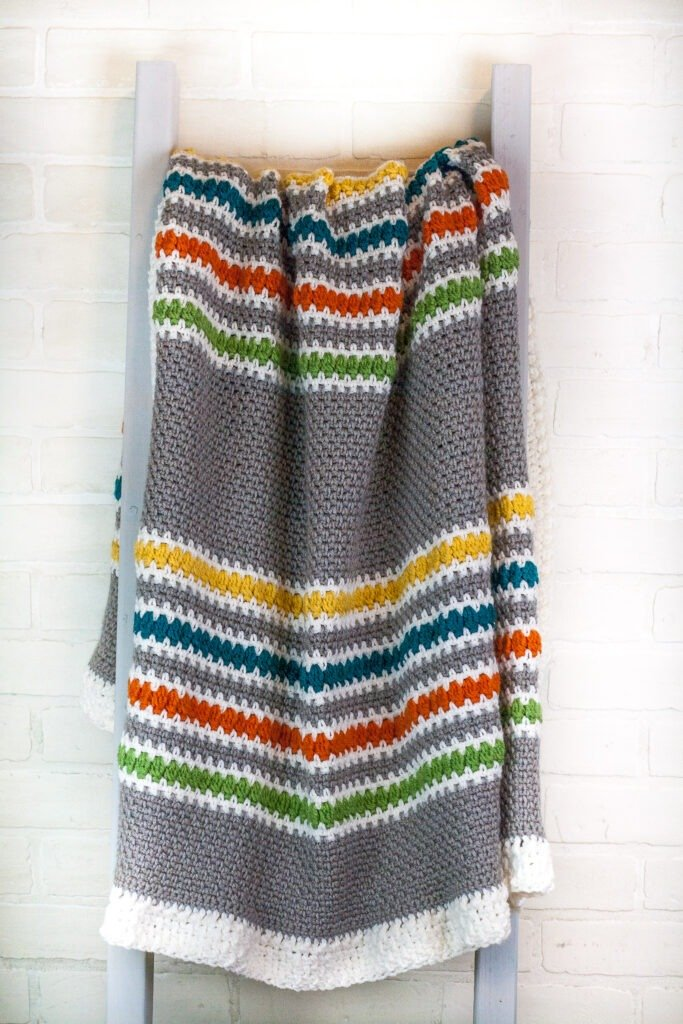 Follow the free crochet pattern and video tutorials to crochet this beautiful modern stripes crochet blanket. Perfect for snuggling in.