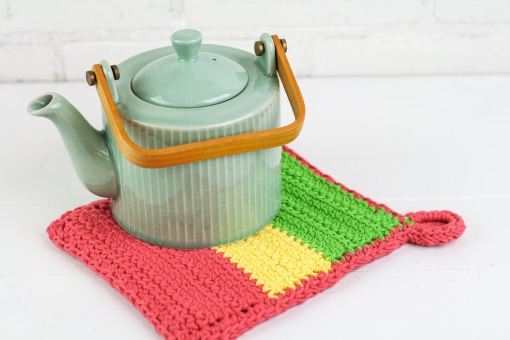 Make a quick, easy and modern crochet potholder with hanging loop. Video tutorials to help guide you through the pattern. Great for using up scrap cotton.