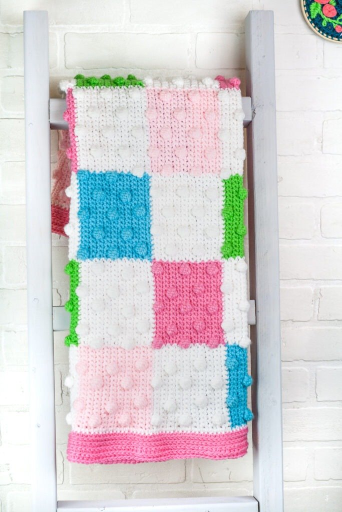 Free crochet pattern for a beautiful and colorful bobble baby blanket. There are 4 added video tutorials to help walk you through how to make this blanket.