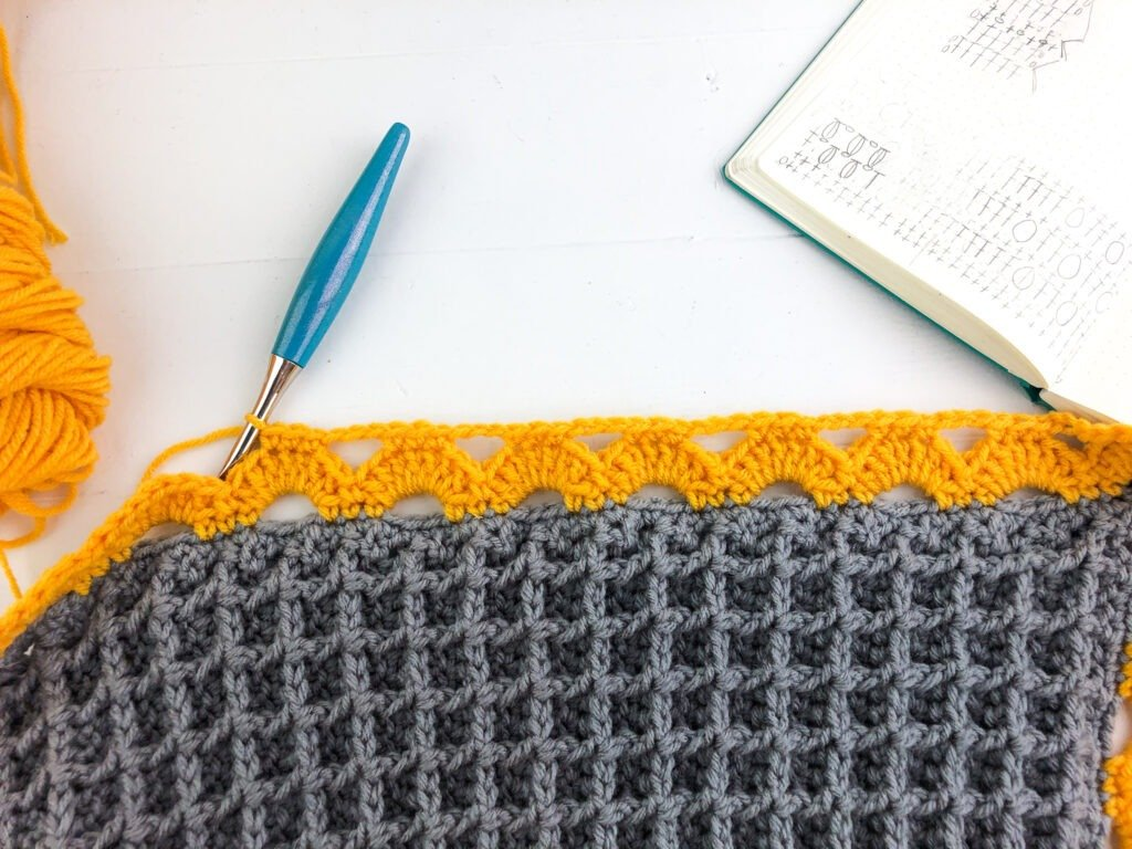 Stunning crochet blanket with a beautiful arcade stitch border. Free crochet pattern with 7 blanket sizes and video tutorials.