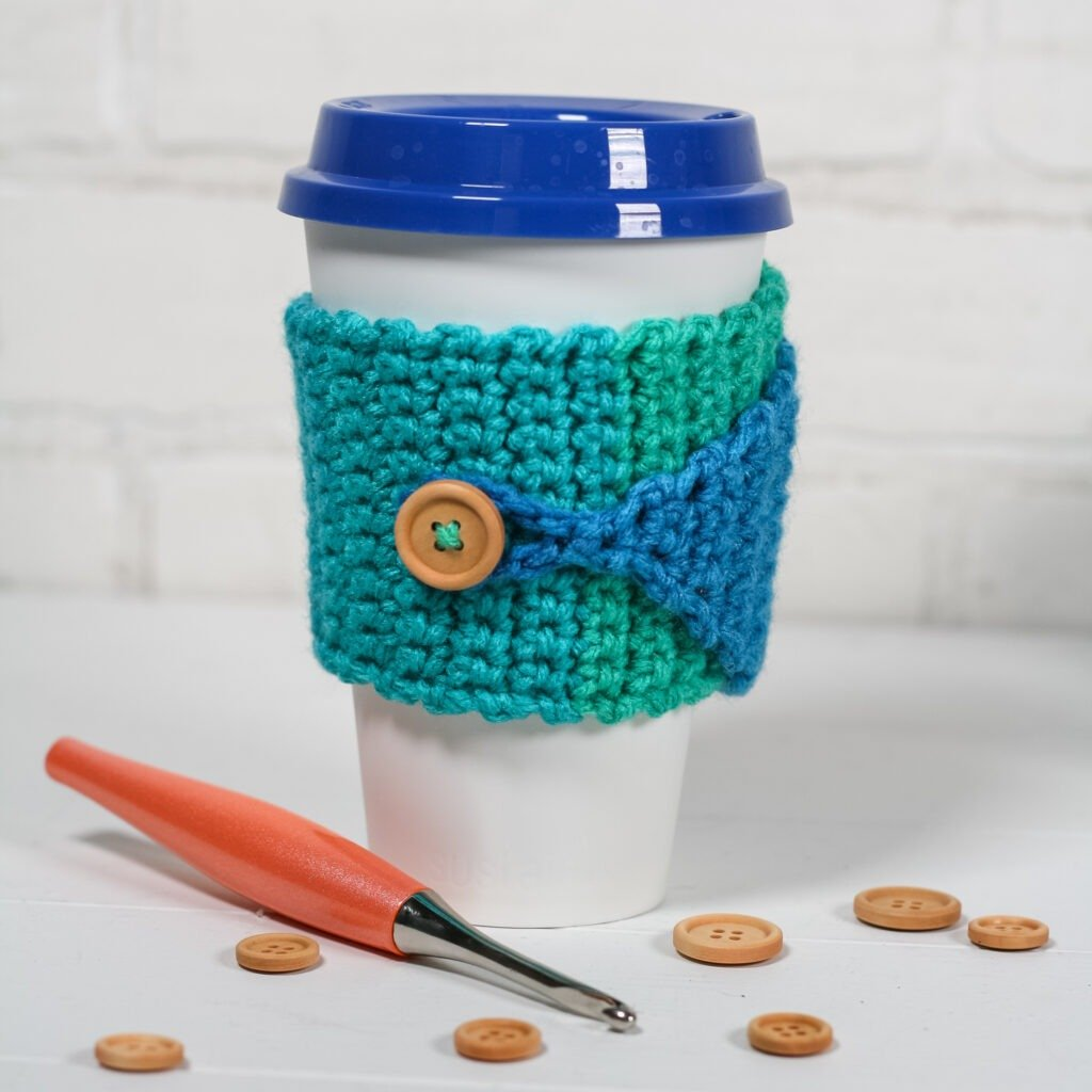 Free crochet pattern for a quick and easy crochet cup cozy with a video tutorial. This cup cozy fits coffee cups and travel mugs.