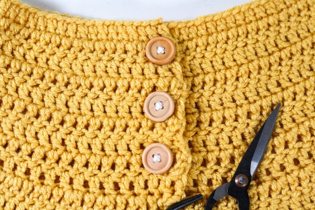 Free crochet pattern for an easy crochet dress for toddlers. This dress uses basic stitches to create a full dress with ruffle sleeves.