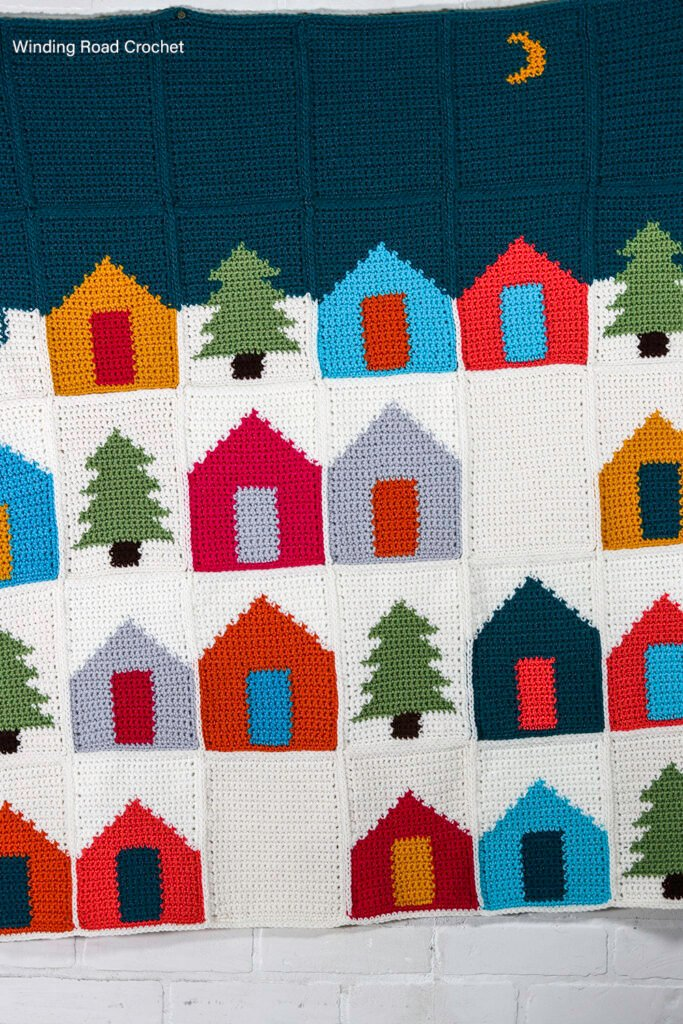Use up your scrap yarn while crocheting this Winter Village Crochet Afghan. The free crochet pattern provides instructions for many sizes.
