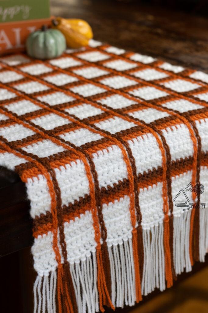 Dekorieren Sie für die Feiertage mit einer kostenlosen Häkelanleitung für einen karierten Tischläufer mit Schottenmuster.  Tartan Plaid kann mit jeder Farbkombination hergestellt werden.