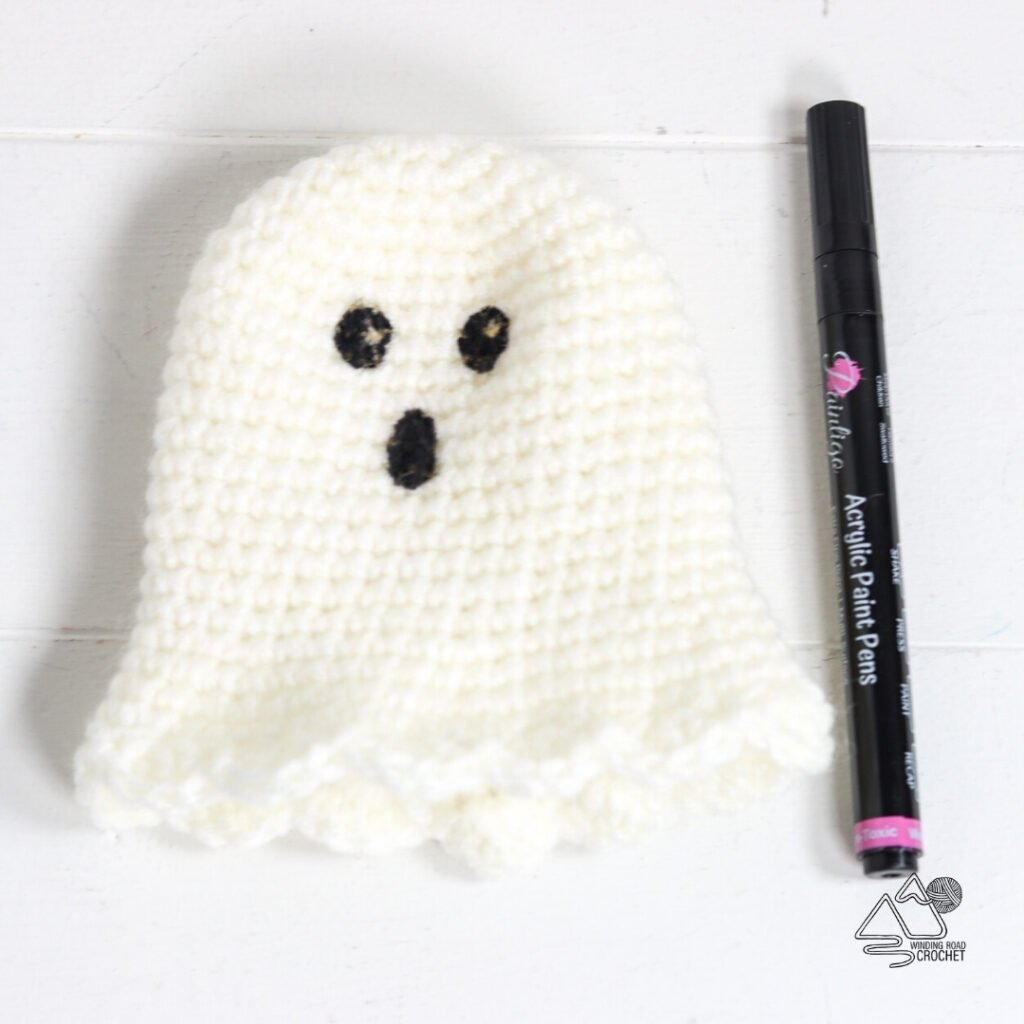 photo of crochet ghost gnome hat with face painted on